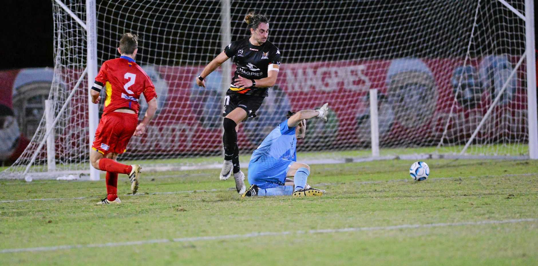 Magpies Crusaders striker Kyle Markham puts a shot past NQ United goalkeeper Daniel Wilesmith in round 15 of the NPL Queensland at Sologinkin Oval, Mackay.