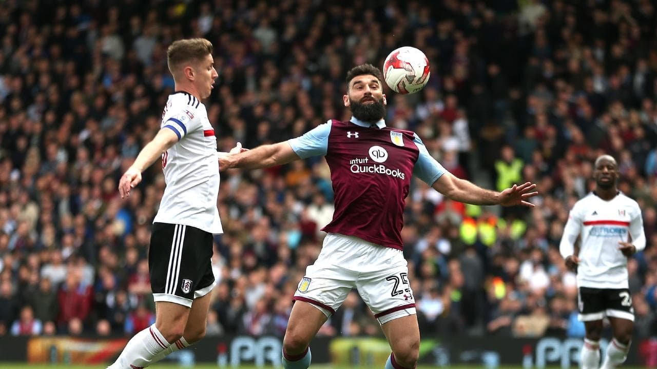 Mile Jedinak of Aston Villa holds off Tom Cairney of Fulham