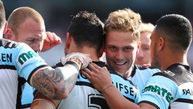 Sharks players celebrate a try against the Knights.