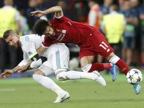 Liverpool's Mohamed Salah (r) goes down hard under the challange from Sergio Ramos.