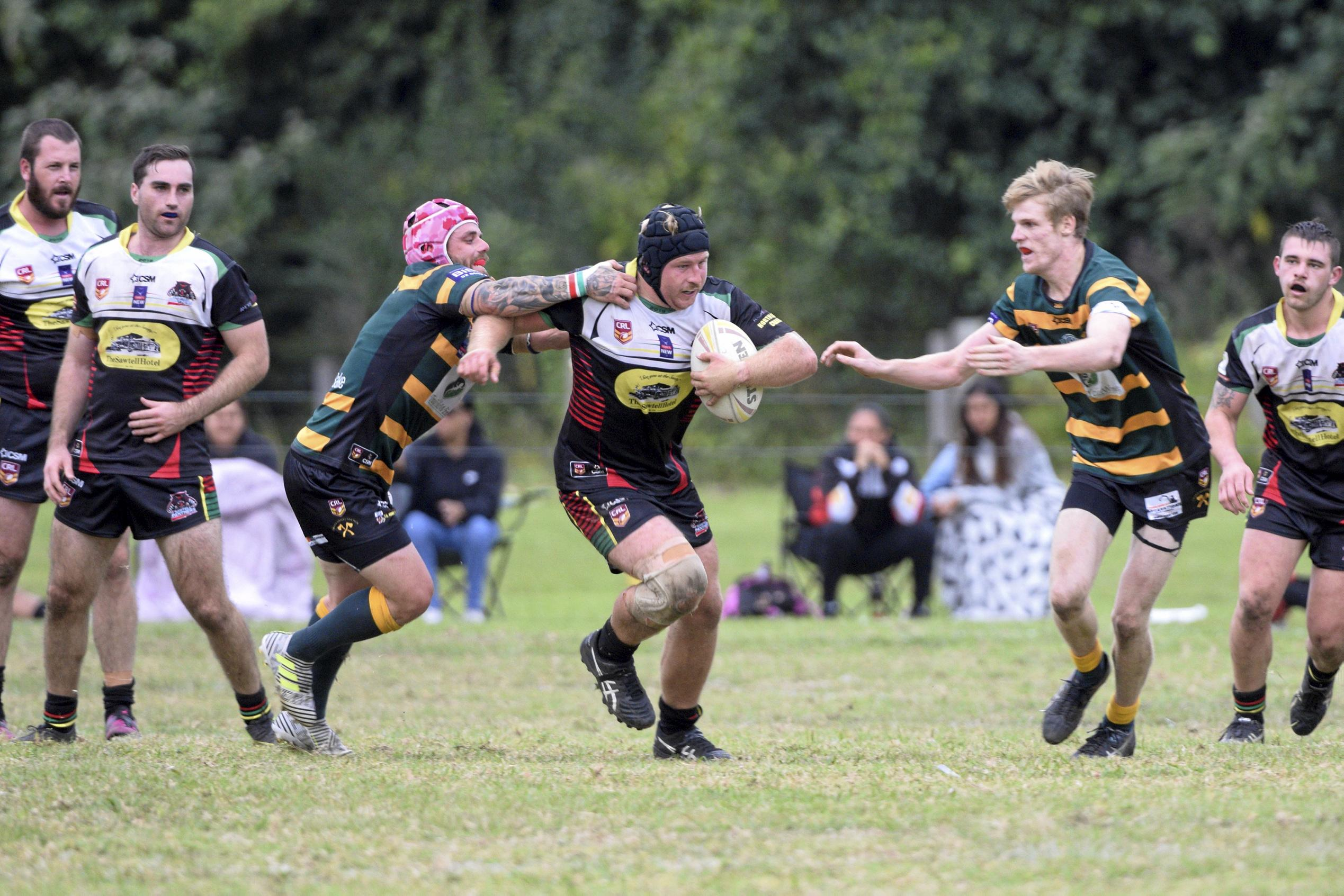 THROUGH THE MIDDLE: Sawtell captain Jedd Mitchell escapes the clutches of Orara Valley pair Rhys Walters and Liam Dunn.