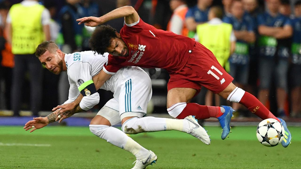 TOPSHOT - Liverpool's Egyptian forward Mohamed Salah (R) falls with Real Madrid's Spanish defender Sergio Ramos leading to Salah being injured