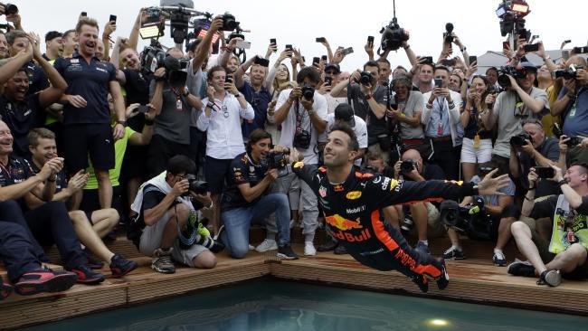 Aussie Red Bull driver Daniel Ricciardo dives into a pool to celebrate his Monaco GP win. Picture: AP/Claude Paris