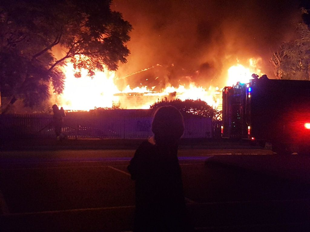 Onlookers watch as fire crews fight a house fire on Fitzgibbon St, North Ipswich last night.
