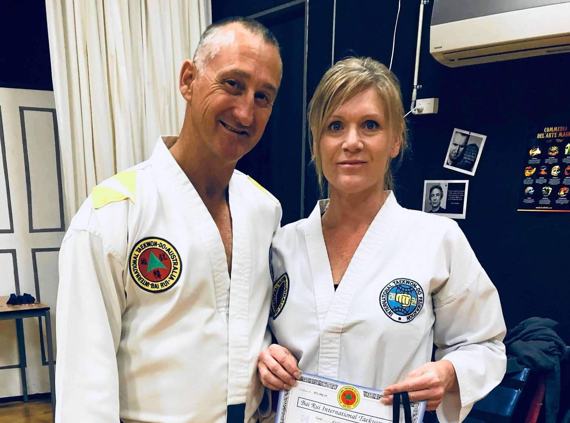 LEVEL UP: Coach Darren Finch with Catherine Ovenden as she receives her taekwondo black stripes.