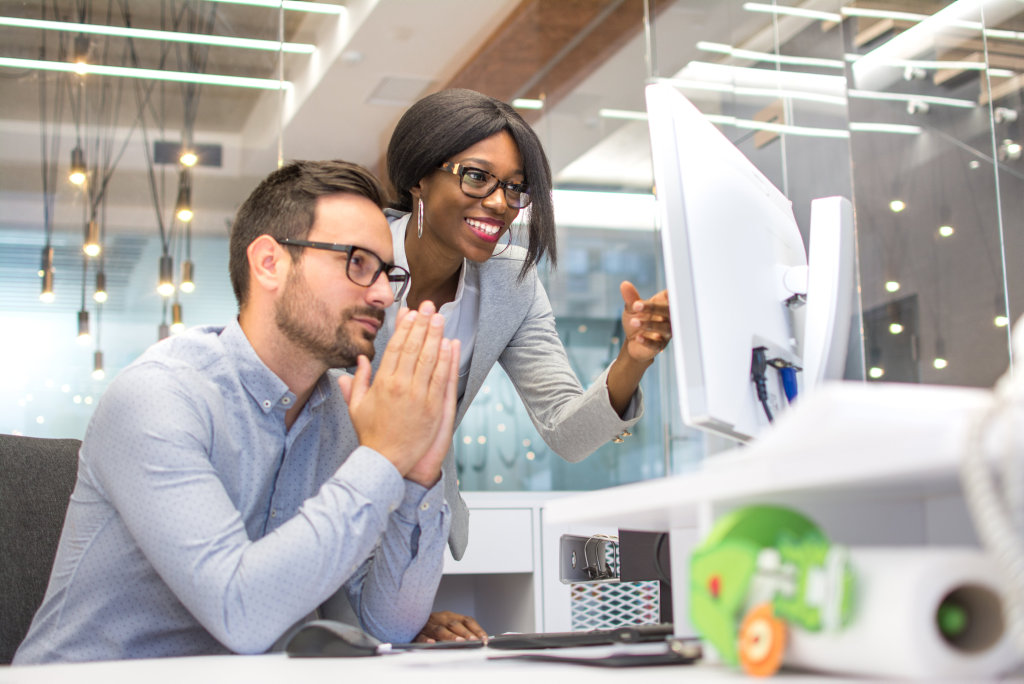 Business colleagues praying for success while looking at project on computer's monitor in office.