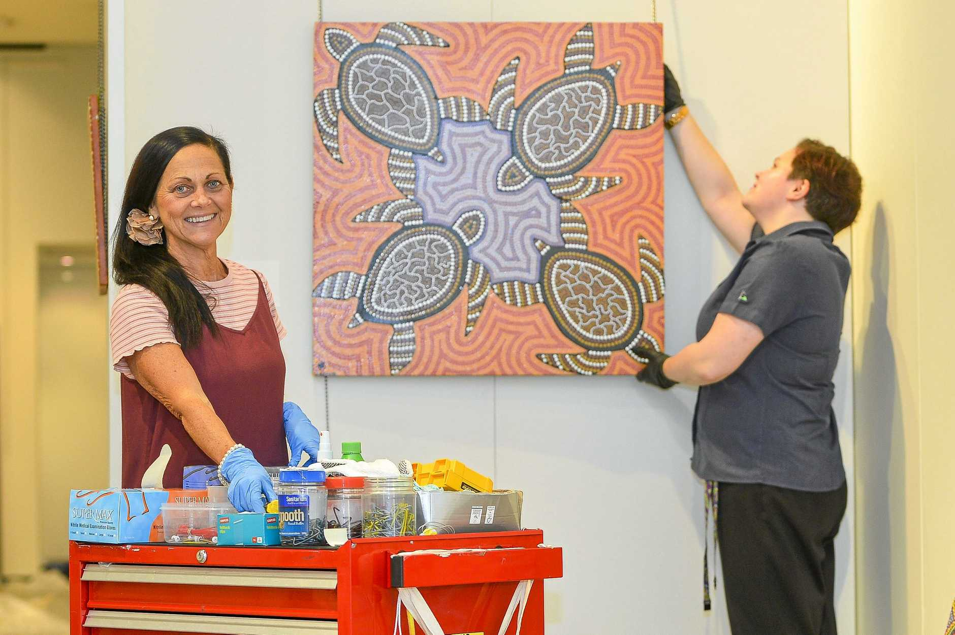 JUST RIGHT: Deleece Lewis, volunteer and Rebecca Lush carefully install the gallery's latest exhibitions.