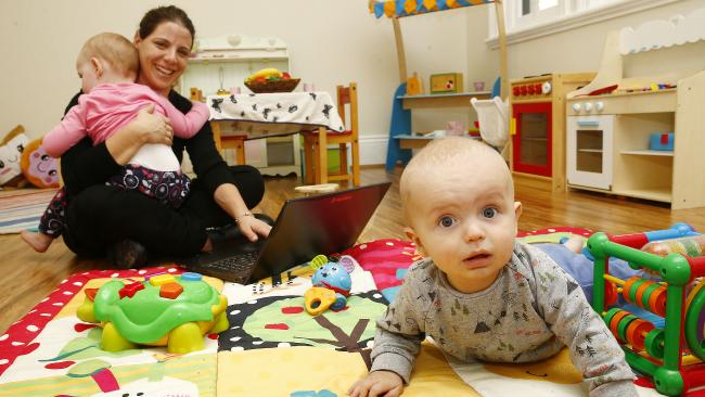 Nicole Traub with baby Finley, six months, and holding Grace, 1, in her in a childcare centre with a 'Bubdesk', a hot desk work space for parents. Picture: John Appleyard