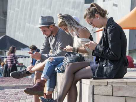 People using their phone in fed square in Melbourne. Picture: Jason Edwards