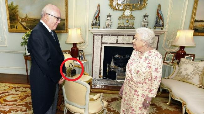 Take a look at the position of the handbag — it's a secret signal from the Queen. Picture: John Stillwell/Pool Photo via AP.