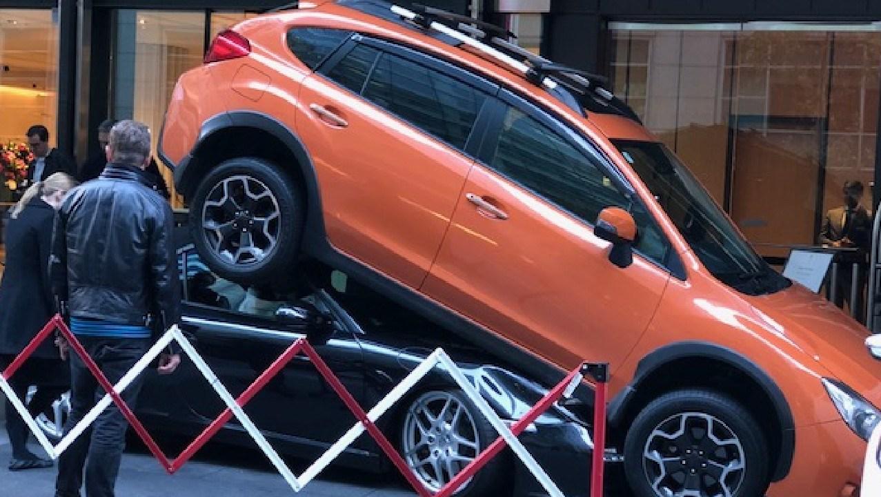 An orange Suburu crushes a black Porsche. Picture: Ben Matthews