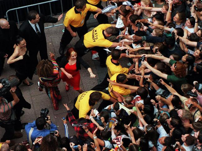 In January 1998 the Spice Girls flew in on a whirlwind tour of Sydney to promote their movie Spice World. Geri is pictured reaching out to fans who crush for a glimpse before they enter the State Theatre. Picture: Brad Newman.