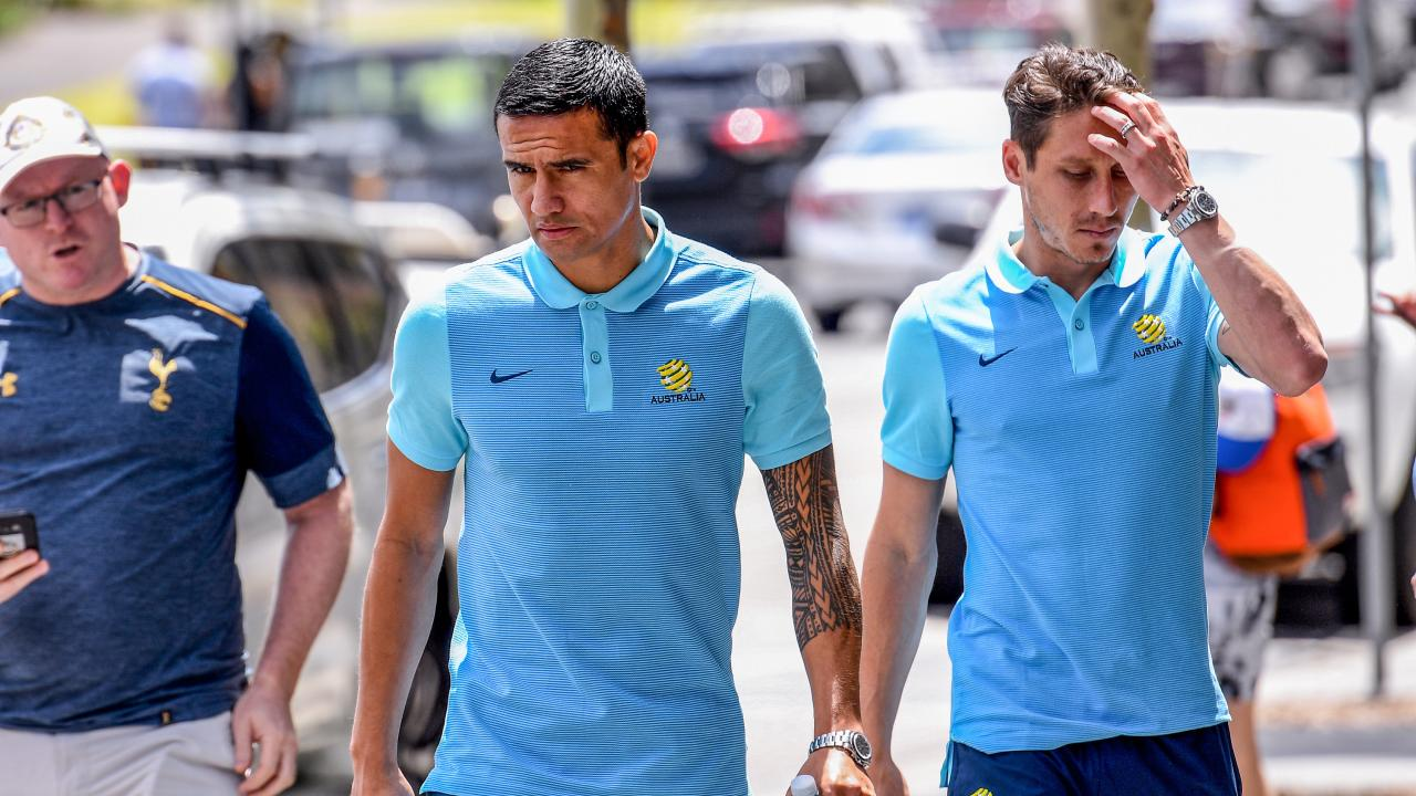 Socceroos players Tim Cahill (centre) and Mark Milligan arrive for a press conference