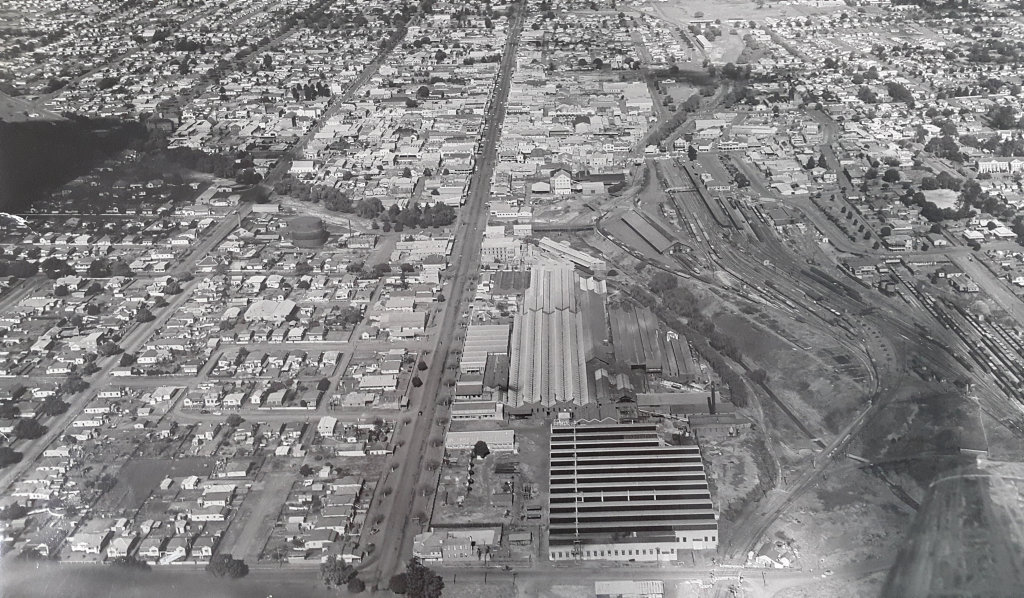 This photo taken early 50's showing Toowoomba Foundry and Arch Campbell's newsagency (bottom left) opposite the recently demolished Marburg Hotel (Rowland's Hotel) on Bridge and Ruthven Streets. Wildman's Sawmill is at the centre bottom of the picture. It is interesting to note the cottage at the Bridge St rail crossing. These houses were generally occupied by widows of men who lost their lives in the service of the railway and their duty was to open and close the railway gates. The rail yards were extensive and very busy with all shunting activities conducted there. Photo Contributed by John Campbell