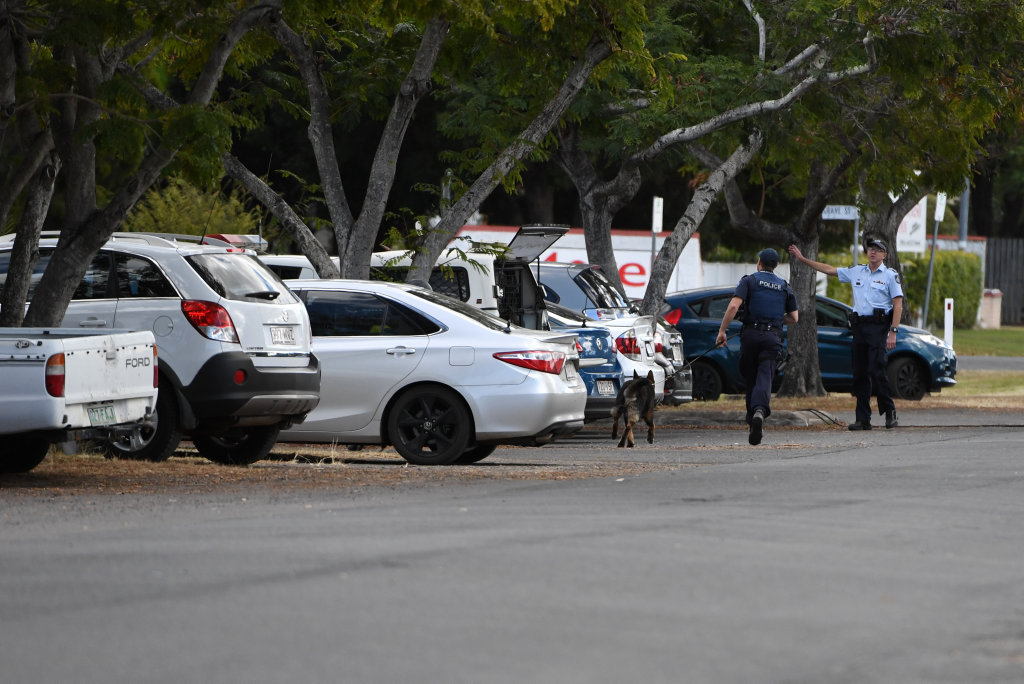 MAN HUNT: Bundaberg police officers run after a man who escaped custody this morning.