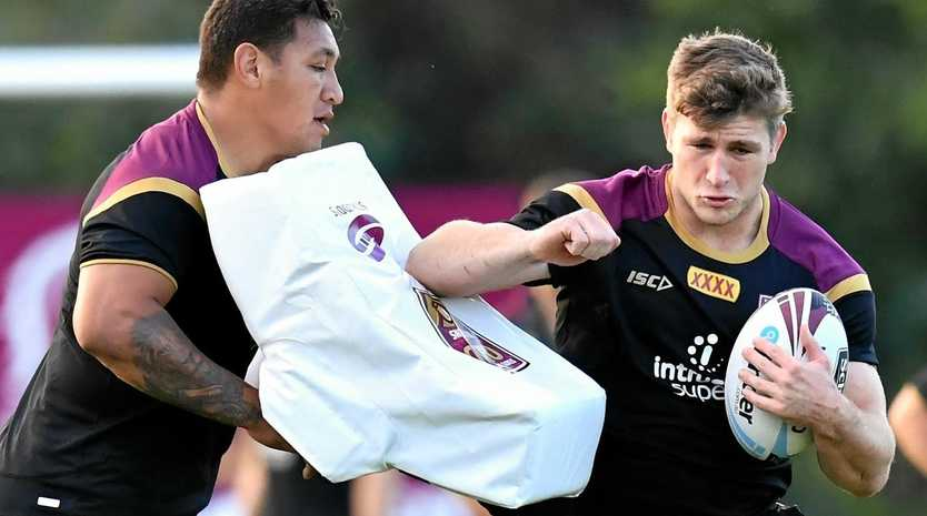 Jai Arrow pushes past Josh Papalii during a Queensland training session.