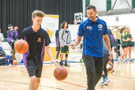 Brisbane Bullets guard Adam Gibson (rright) guides St Joseph's College student Jeremy Dagg through a dribbling skill.