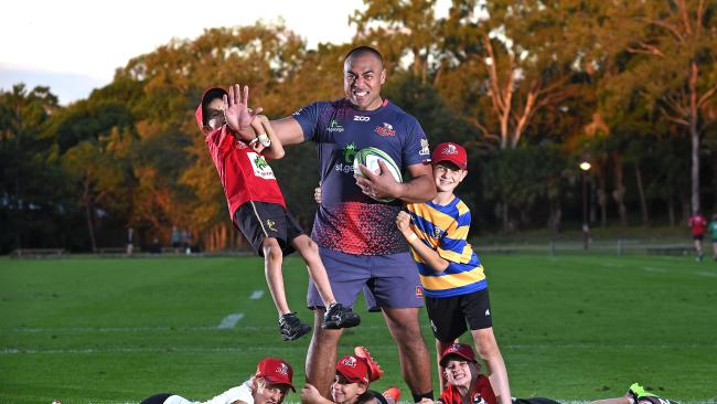 Reds forward Caleb Timu at Ballymore with kids for a training session.