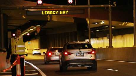 Brisbane Mayor Graham Quirk waves the first few cars into the Legacy Way tunnel at its opening. Picture: Marc Robertson