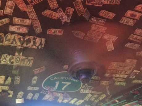 The ceiling of the rough and ready establishment is plastered with dollar bills scrawled with names and swearwords.