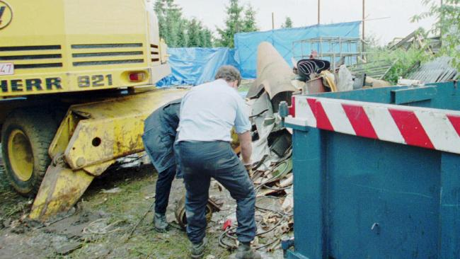 Policemen search for remains in the yard of a house near where Dutroux imprisoned children.
