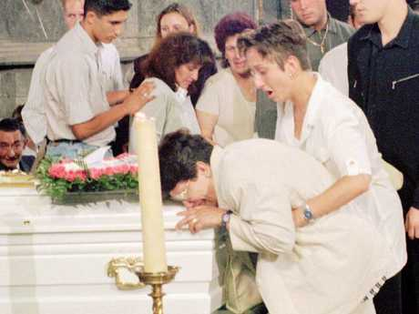 A weeping relative clutches the coffin of Melissa Russo who Dutroux starved to death.