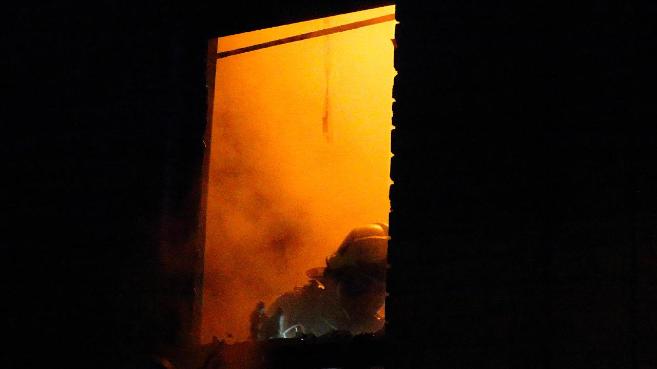 A firefighter clears the passage way next to a window at the West Footscray home. Picture: Patrick Herve.