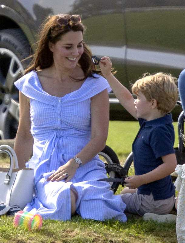 Britain's Kate, the Duchess of Cambridge , left smiles at Prince George as they watch Prince William take part in the Maserati Royal Charity Polo Trophy at the Beaufort Polo Club, in Tetbury, England, Sunday June 10, 2018. (Steve Parsons/PA via AP)