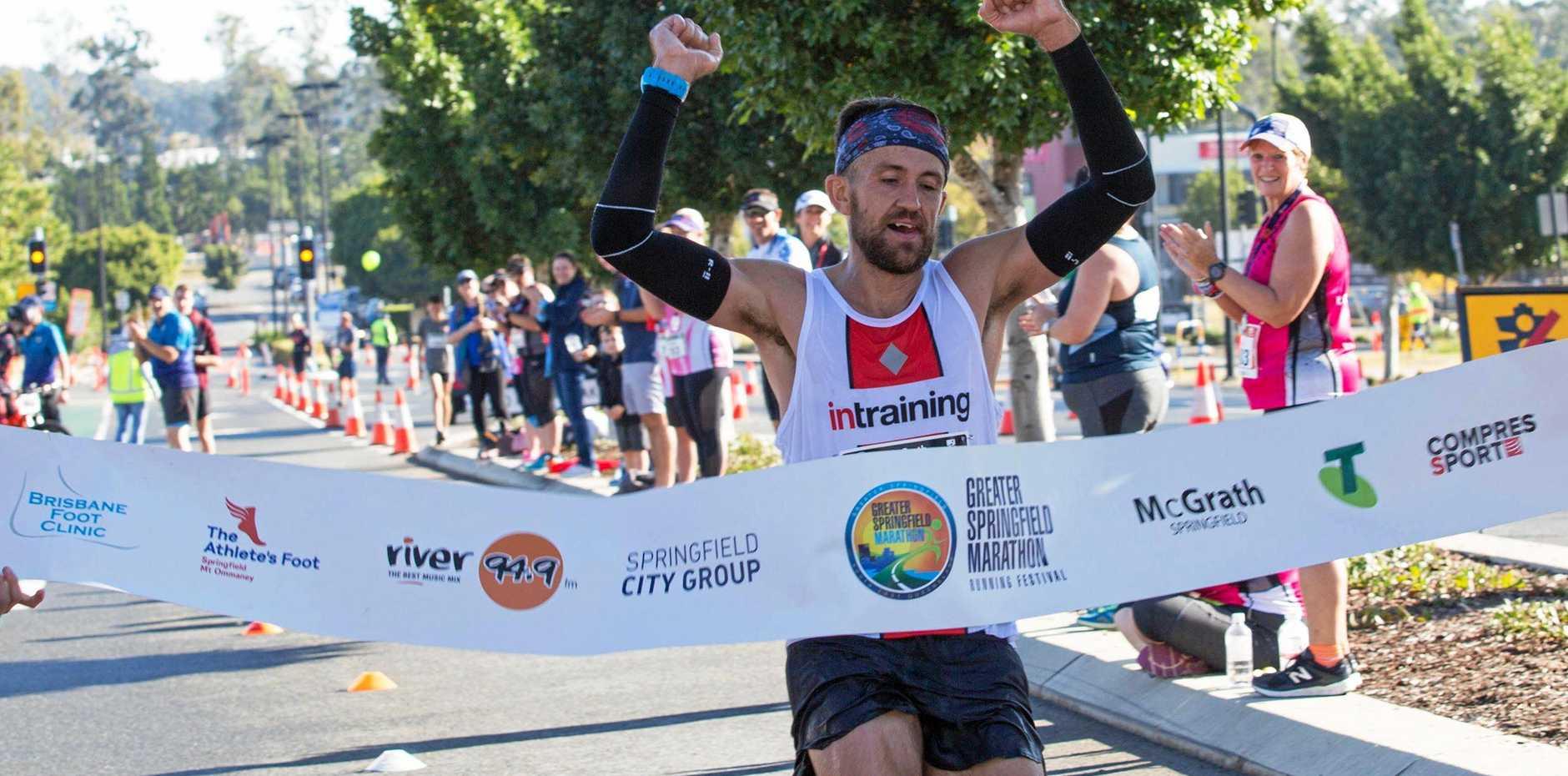 FANTASTIC FINISH: Ipswich marathon ace Clay Dawson crosses the line first to win the inaugural Greater Springfield Marathon.