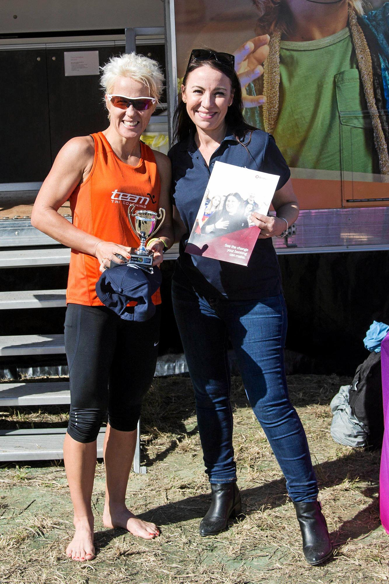 Top female marathon winner Taryn Axelsen receives her winner's trophy and cheque from Tracey Caruana, the principal of marathon sponsors McGrath Springfield.