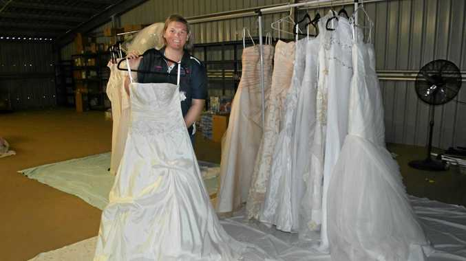 WEDDING BELLS: Drought Angel's Event Coordinator Carissa Liddle with just some of the dresses donated to the charity.
