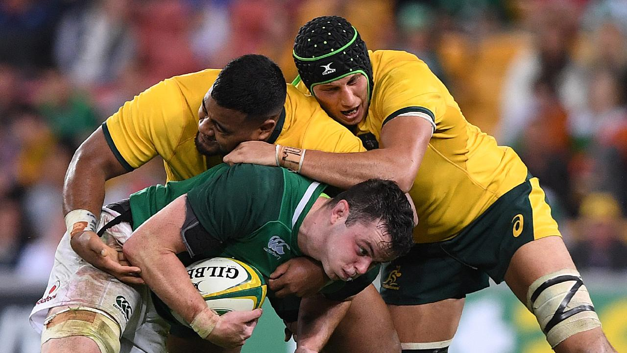 James Ryan of Ireland is tackled by Taniela Tupou (left) and Adam Coleman of the Wallabies.