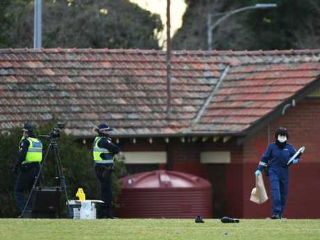 Victorian Police Forensic Officers work at the scene. A pair of shoes can be seen near the body. Picture: James Ross/AAP