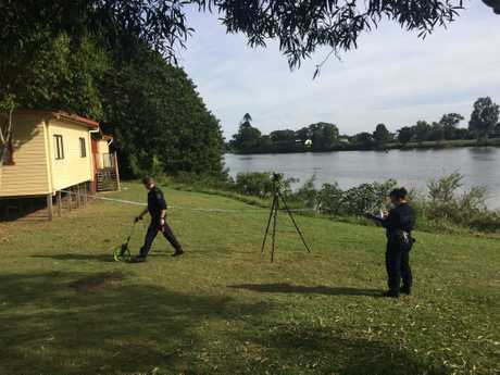 Police conduct a forensic examination at the memorial hall on the banks of the Richmond River at Woodburn after a man went missing in the river last night.