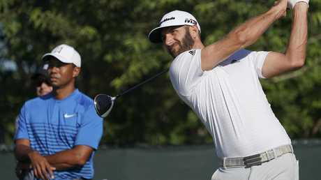 Dustin Johnson hits off the fourth tee as Tiger Woods watches on.