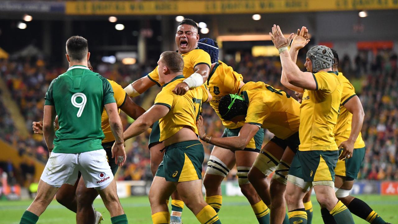 Tolu Latu (centre) of the Wallabies celebrates after Australia won a scrum penalty against Ireland at Suncorp Stadium.