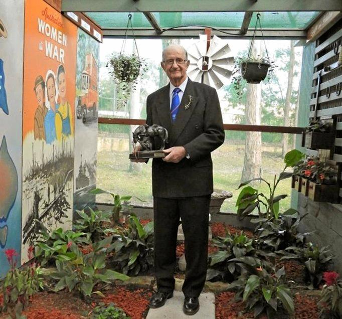 PROUD: Artist Peter Skinner in the Armistice Centenary Garden with his murals in the background, holding a statue of a Waler ¬- an Aussie horse used by the thousand in the First World War.