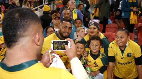 The Wallabies' Tolu Latu takes a picture of Sekope Kepu and his family.