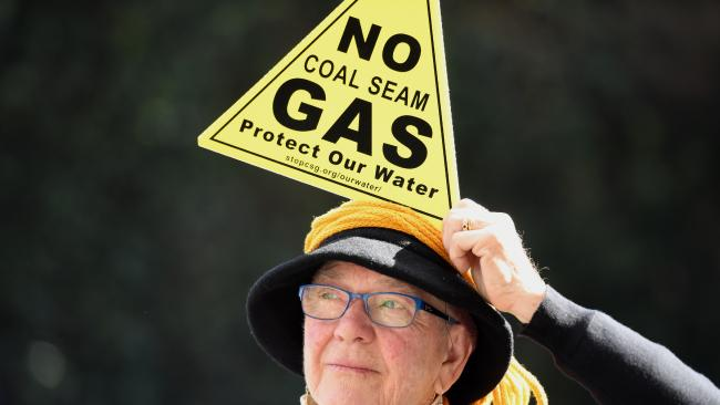 A Sydney demonstrator holds a placard to protest against Santos' plans for a major coal seam gas field near Narrabri, in northwestern NSW, last August.