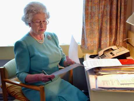 Queen Elizabeth II works at her desk on the Royal Train in May 2002. Picture: Anwar Hussein/Getty Images