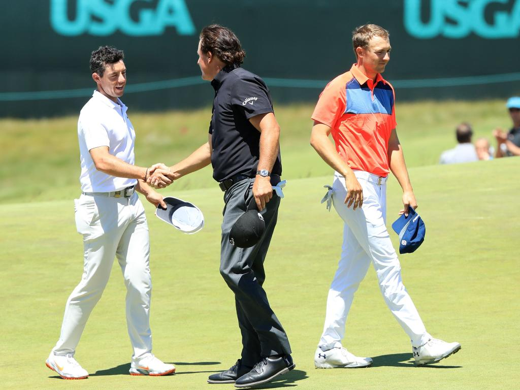 (L-R) Rory McIlroy of Northern Ireland and Phil Mickelson of the United States shake hands as Jordan Spieth of the United States walks off on the ninth hole.