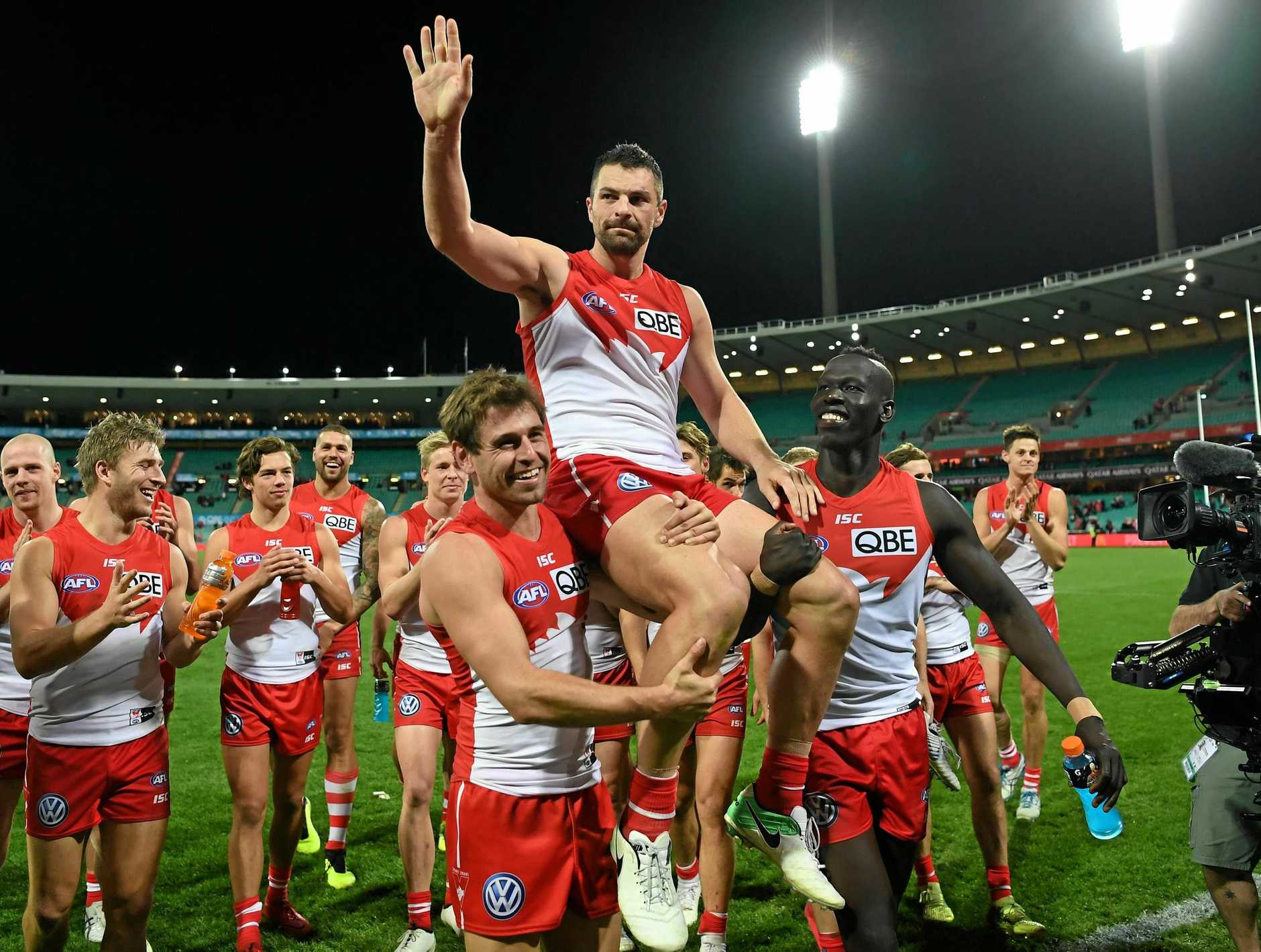 The Swans' Heath Grundy is carried off the ground by his teammates after playing his 250th match on Friday night in Sydney's clasdh with West Coast. Picture: David Moir/AAP