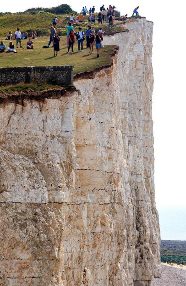 Tourists stroll dangerously close to the edge of cliffs at Beachy Head, East Sussex, where more than 500 people have died since 1965. Picture: Mirrorpix/australscope