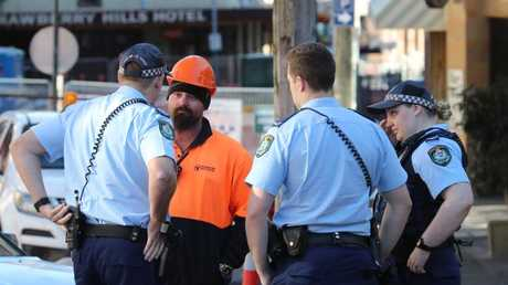 Police speak to a construction worker on Devonshire Street.