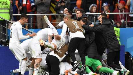 Uruguay players celebrate after defender Jose Gemenen's opening goal.