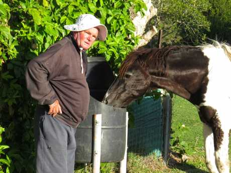 Kenny at the back of his home feeding the Brooms Head brumby.