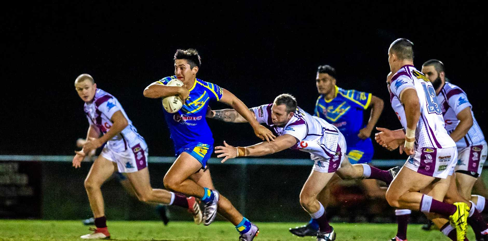 Lachlan Garrels of the Gympie Devils makes a break for it from Kawana's defenders.