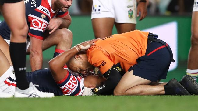 Latrell Mitchell receives attention from a trainer after injuring his neck in a tackle. (AAP Image/Brendon Thorne)