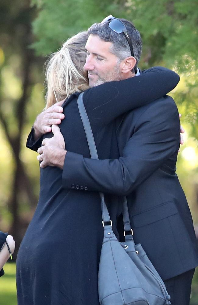 Aaron Cockman (right) is greeted by family and friends outside Bunbury Crematorium before the funerals of his ex-wife Katrina Miles and their four children, daughter Taye 13, and sons Rylan 12, Arye 10, and Kayden 8, in Bunbury, south west of Perth, Wednesday, May 30, 2018. (AAP Image/Richard Wainwright) NO ARCHIVING