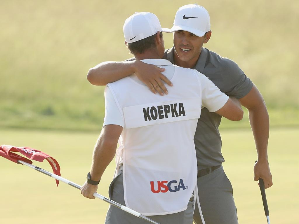 Brooks Koepka of the United States and caddie Richard Elliott celebrate on the 18th green during the final round of the 2018 U.S. Open at Shinnecock Hills Golf Club.